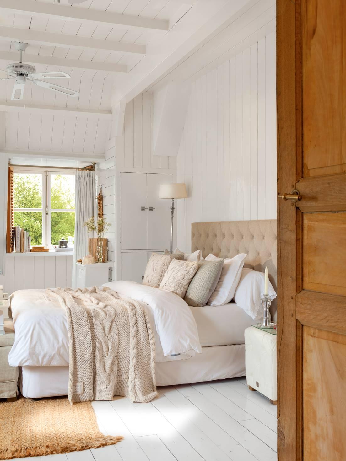 Dormitorio con vigas blancas y ventilador cabecero en tonos beige_408203