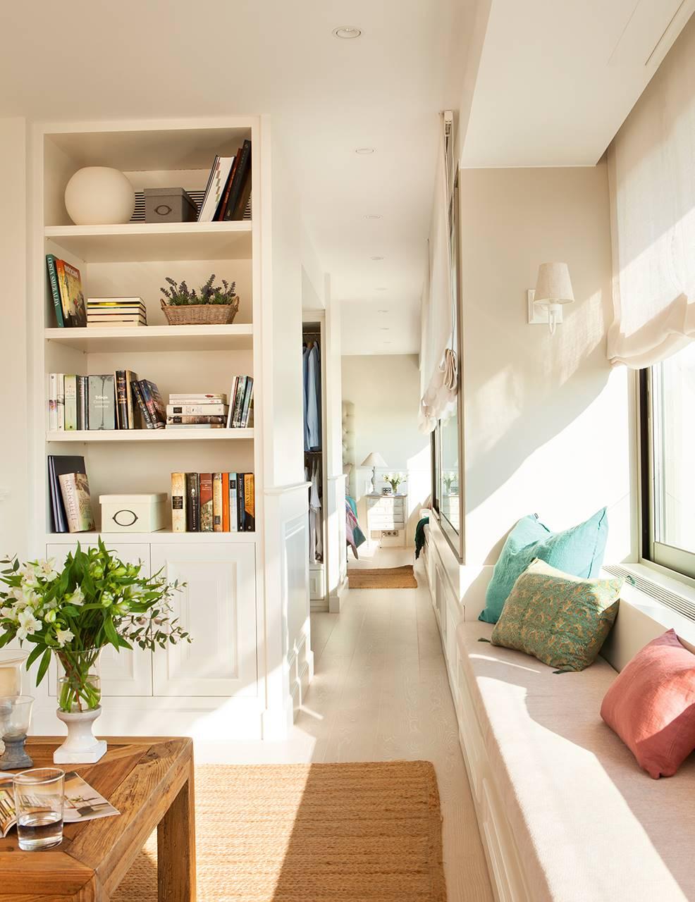 Pasillo que une el salón y el dormitorio con el vestidor en medio. Tonos neutros, cojines de colores, librería, estores y luz natural.. El Feng Shui y la luz natural