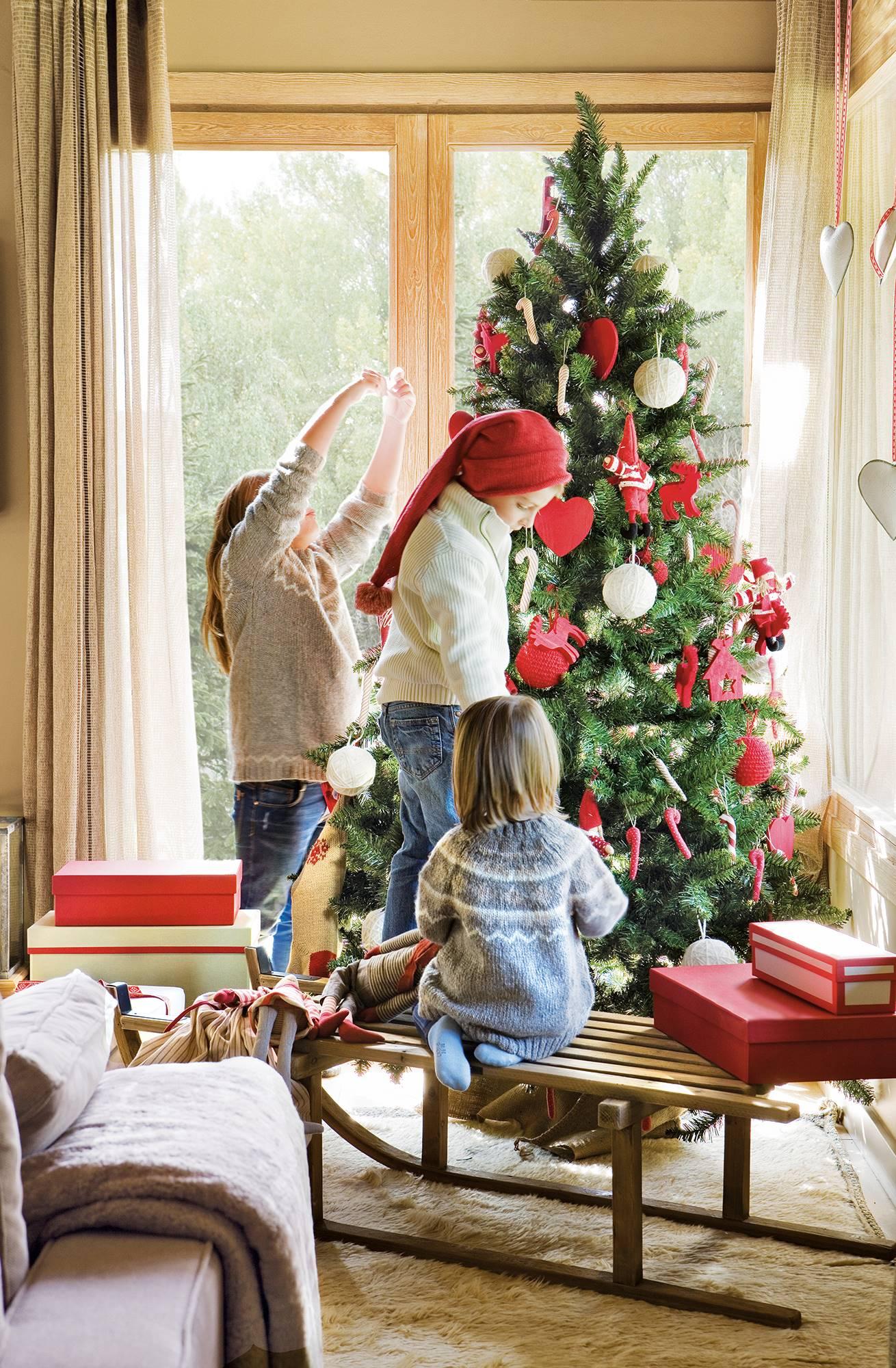 31049612acc8d Árbol de Navidad con adornos rojos y blancos y niños decorándolo  00374144.  Pueden reutilizarse como
