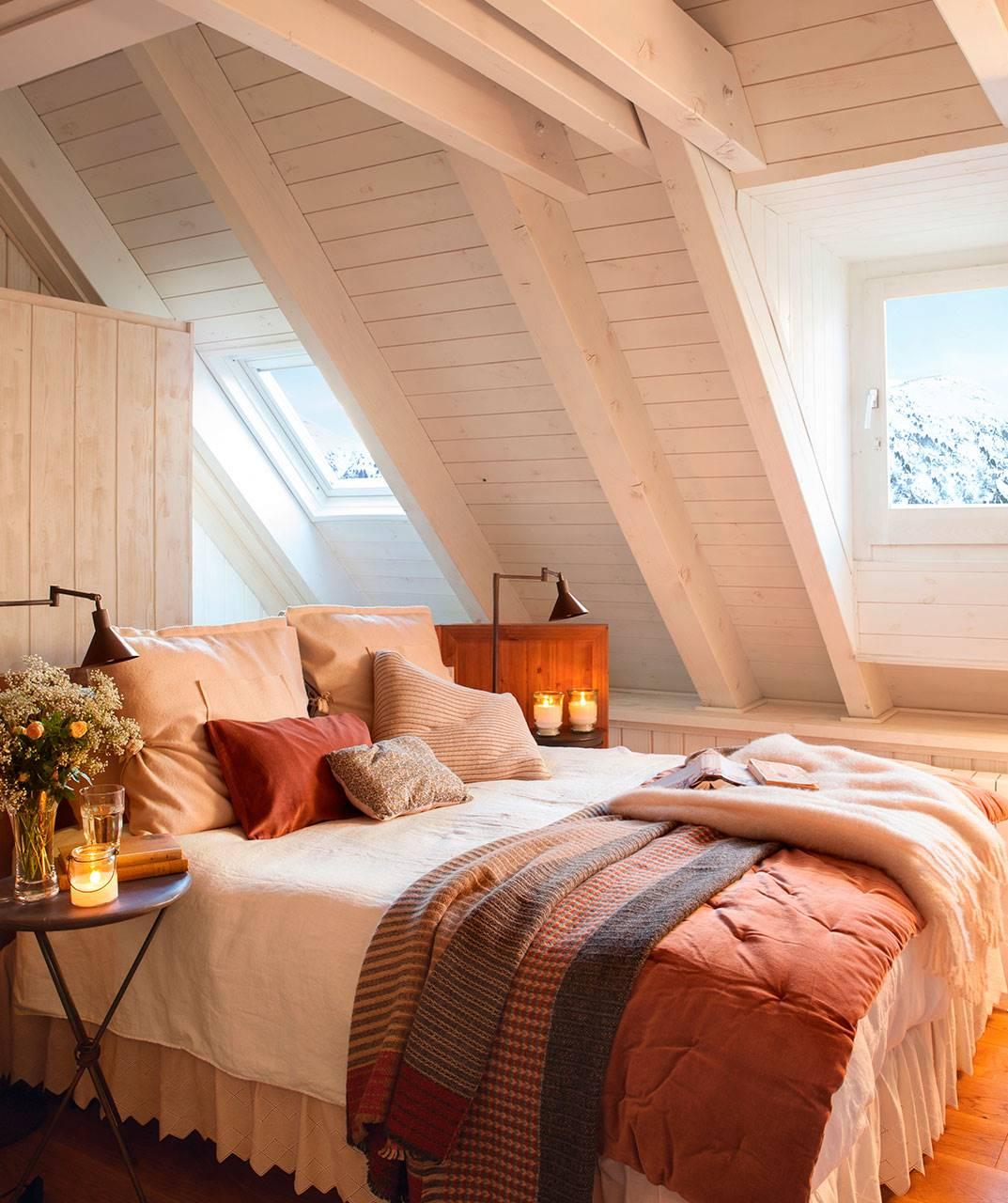 dormitorio-rustico-con-techo-abuhardillado-en-madera-blanca-y-cama-con-textiles-rojos 2ae35858. El romanticismo del estilo rústico
