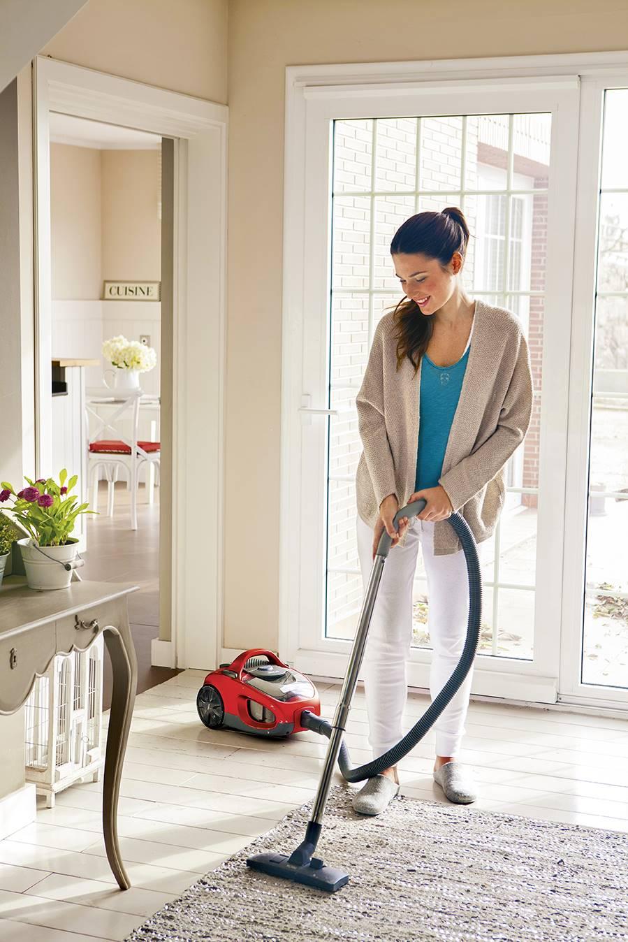 Chica con aspirador limpiando el recibidor_392982. Empezar de abajo hacia arriba