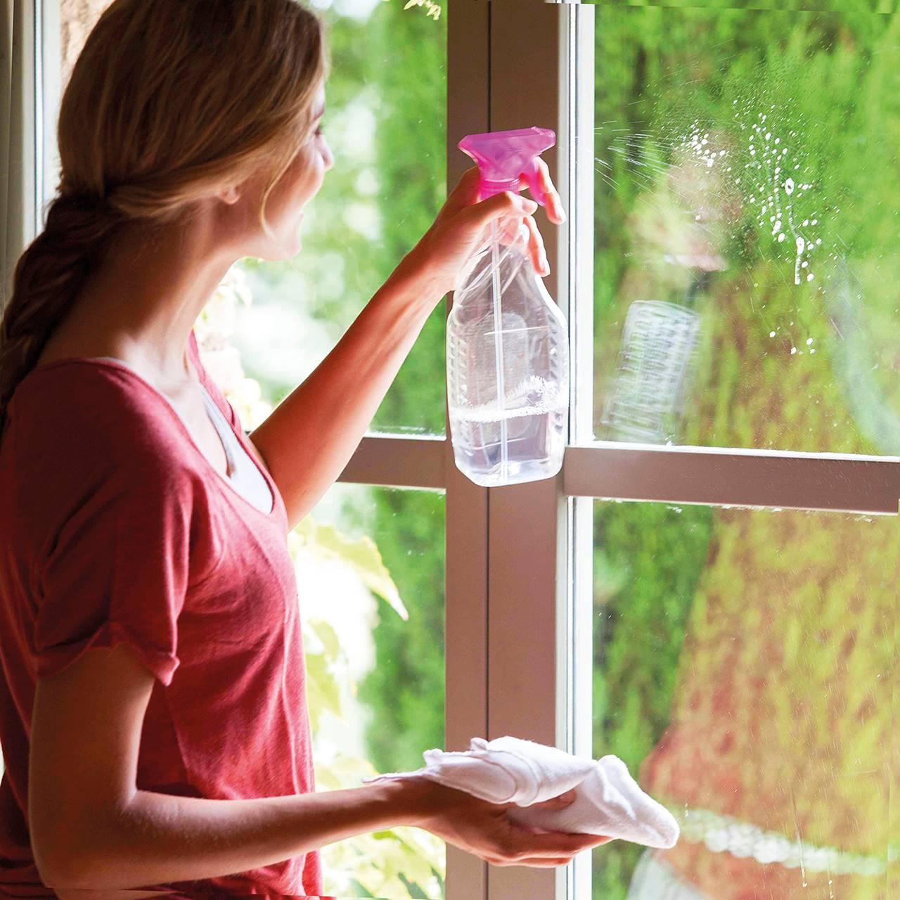 Mujer con limpicristales limpiando una ventana. Aplicar el producto directamente