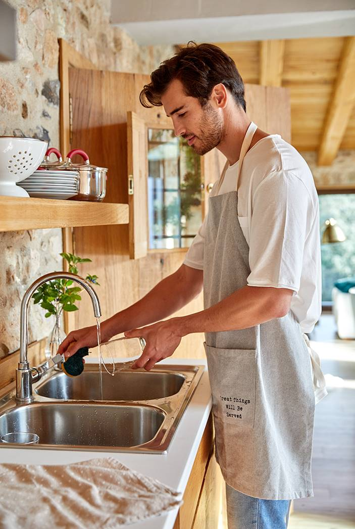 hombre lavando platos. Recoger antes de acostarse