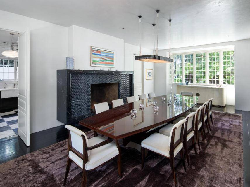 marble-fireplace-anchors-dining-room-can-seat-20-people. Un comedor de cine