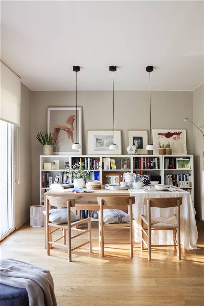 Mesa de comedor de madera con lamparas colgantes y librería blanca de pared a media altura 00493650_O