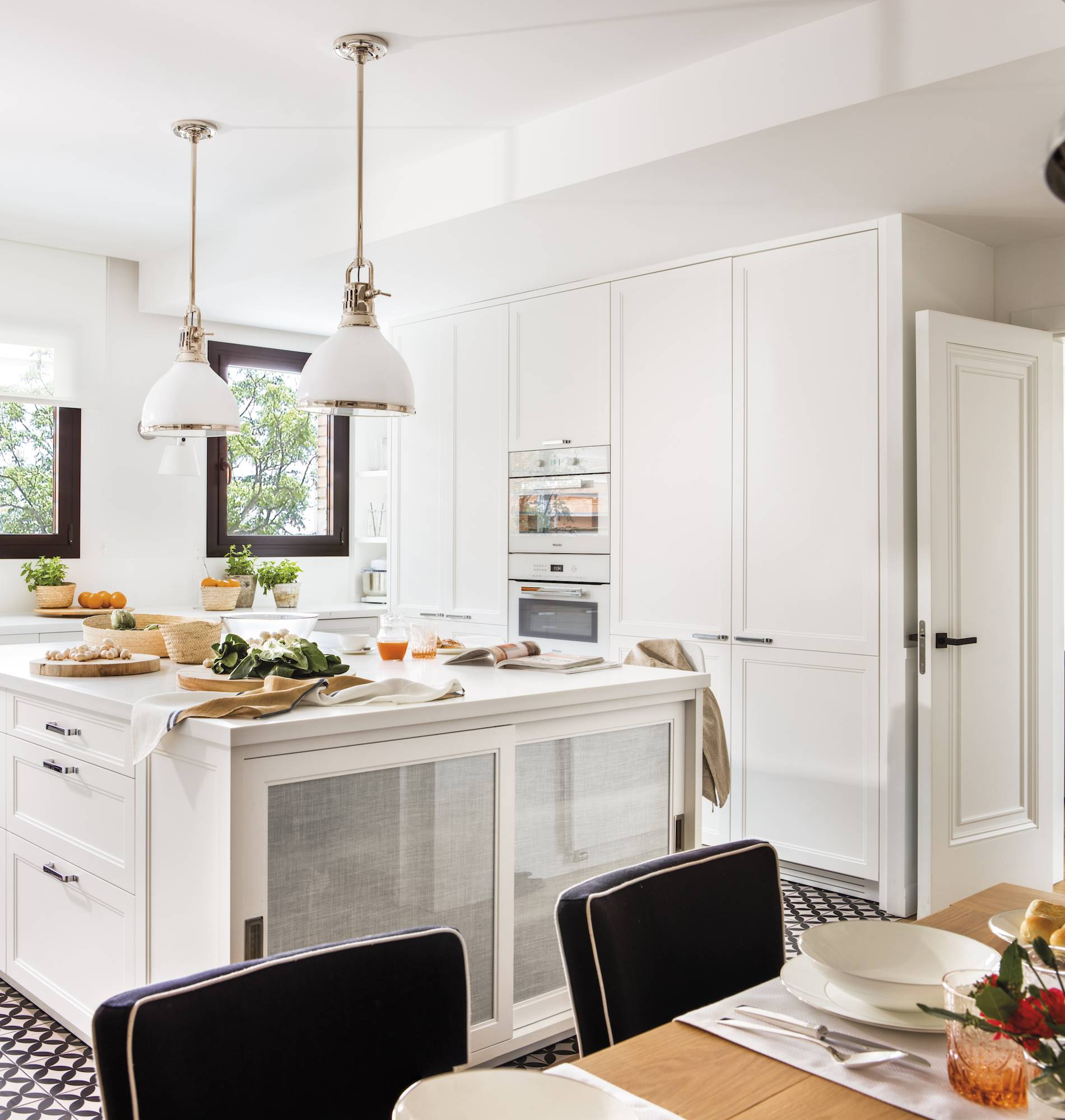 white kitchen with island two ceiling lamps.  Tapped up to the roof