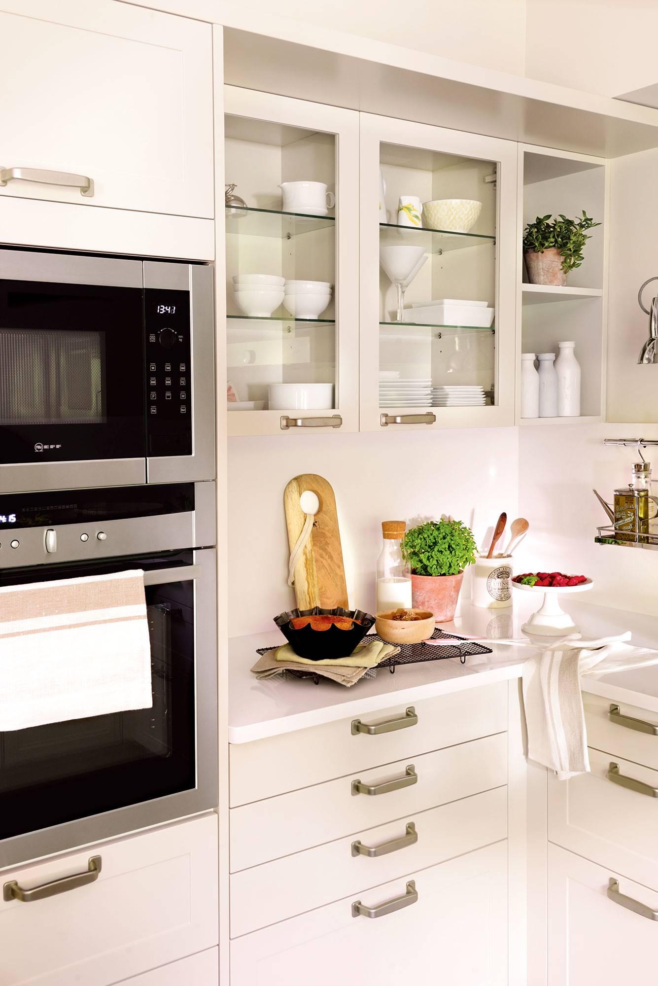 Semitoma cocina con muebles en blanco, cajones, vitrinas y horno y microondas en columna. Microondas