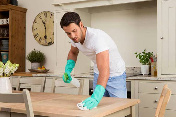 hombre limpiando la mesa. Encimeras y mesa de la cocina