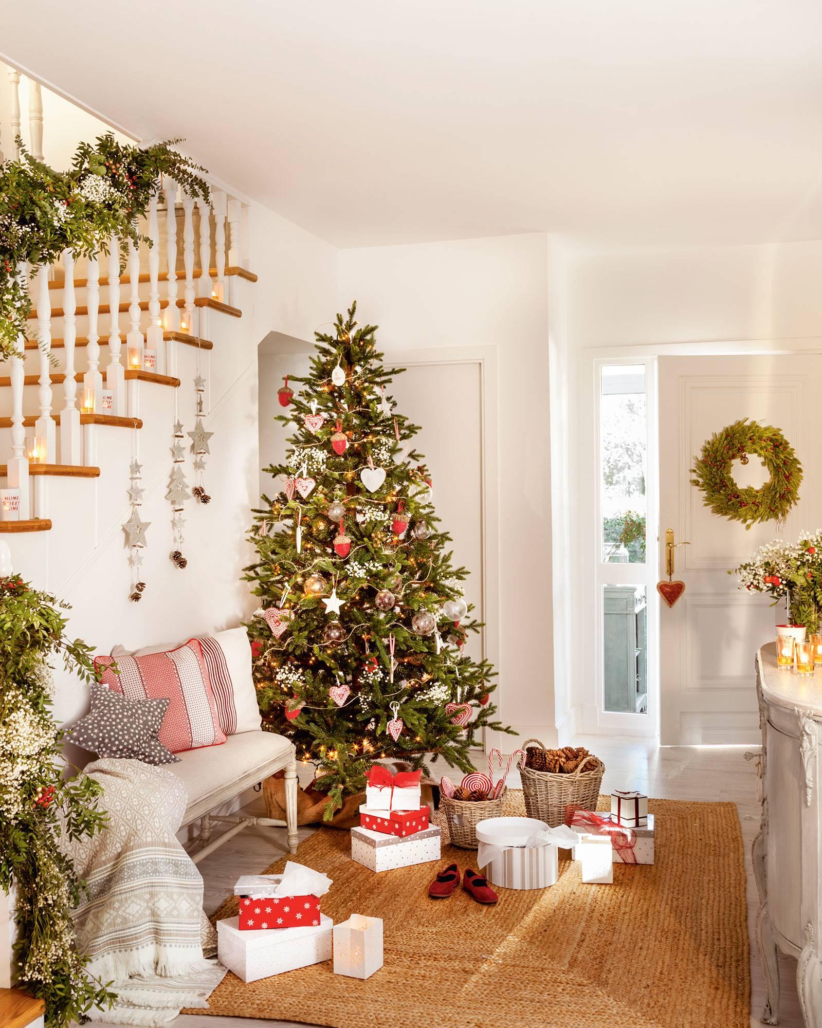recibidor blanco con escaleras y árbol de Navidad con adornos rojos. Los tres colores de la Navidad y del Feng Shui