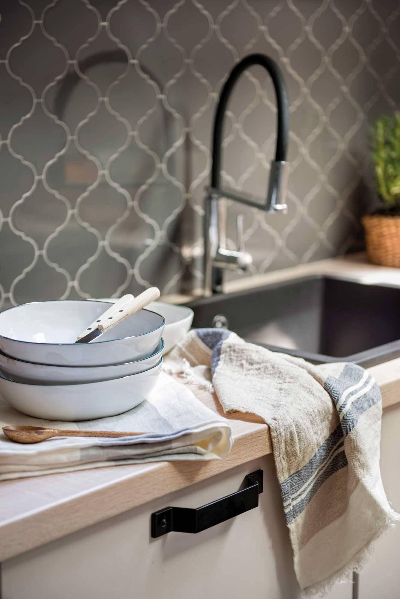 cocina-con-platos-apilados-junto-al-fregadero-00507379. Los platos de la bandeja inferior no salen tan limpios como los de la superior