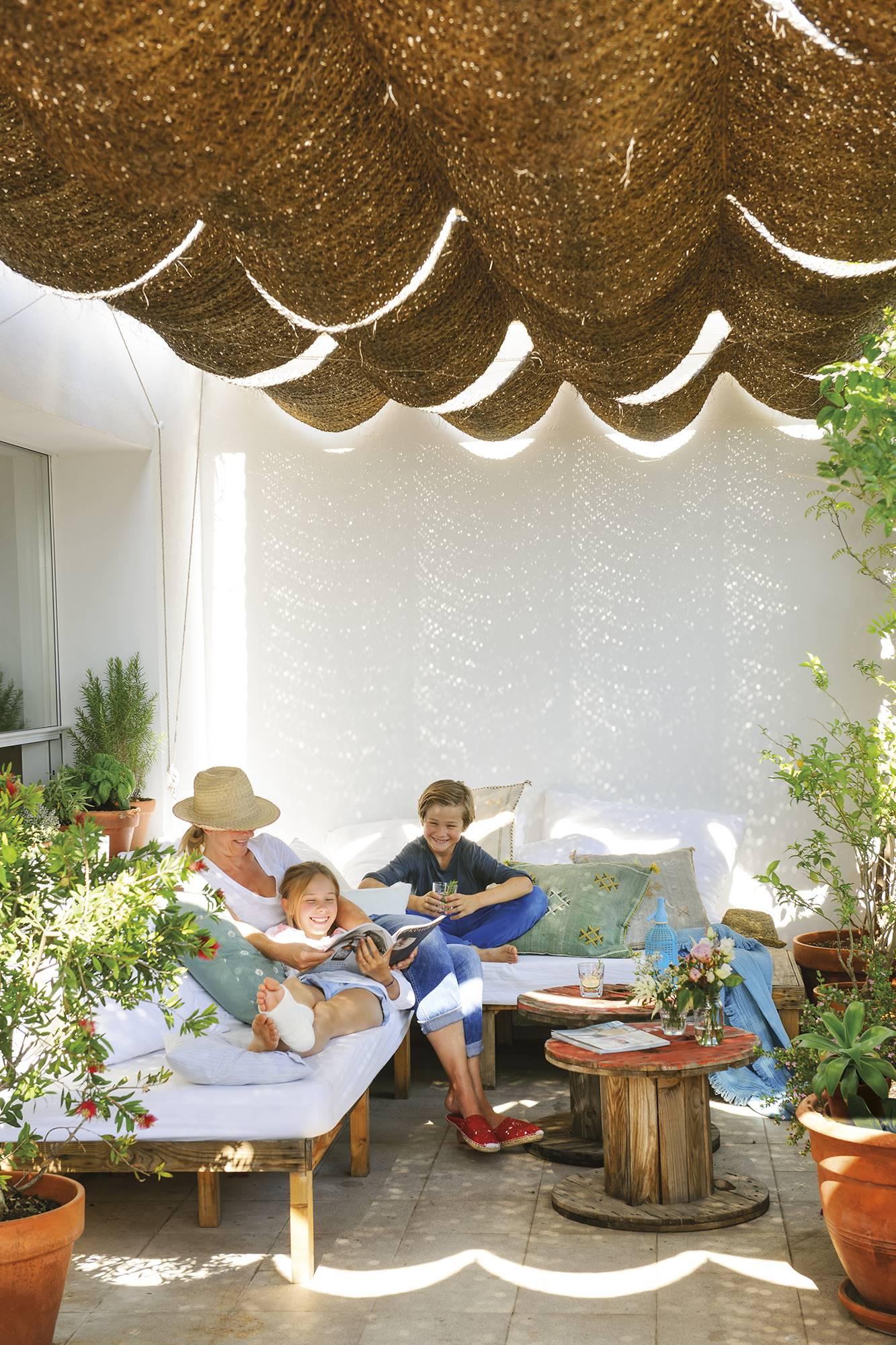 Familia en el porche de su casa. 1. Un dúplex en la ciudad que parece una casita mediterránea
