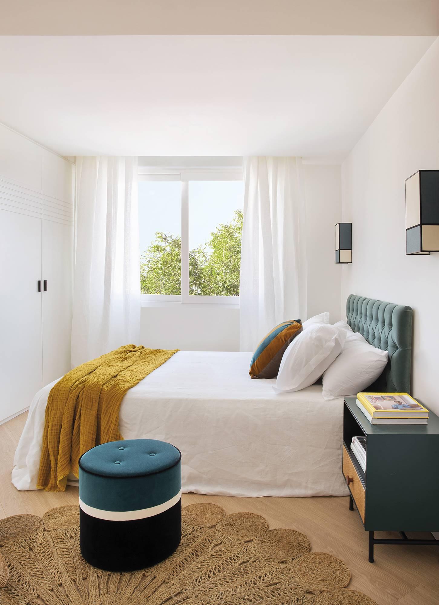 Dormitorio en blanco con toques de azul en cabecero y puff de terciopelo. Un blanco que no falla