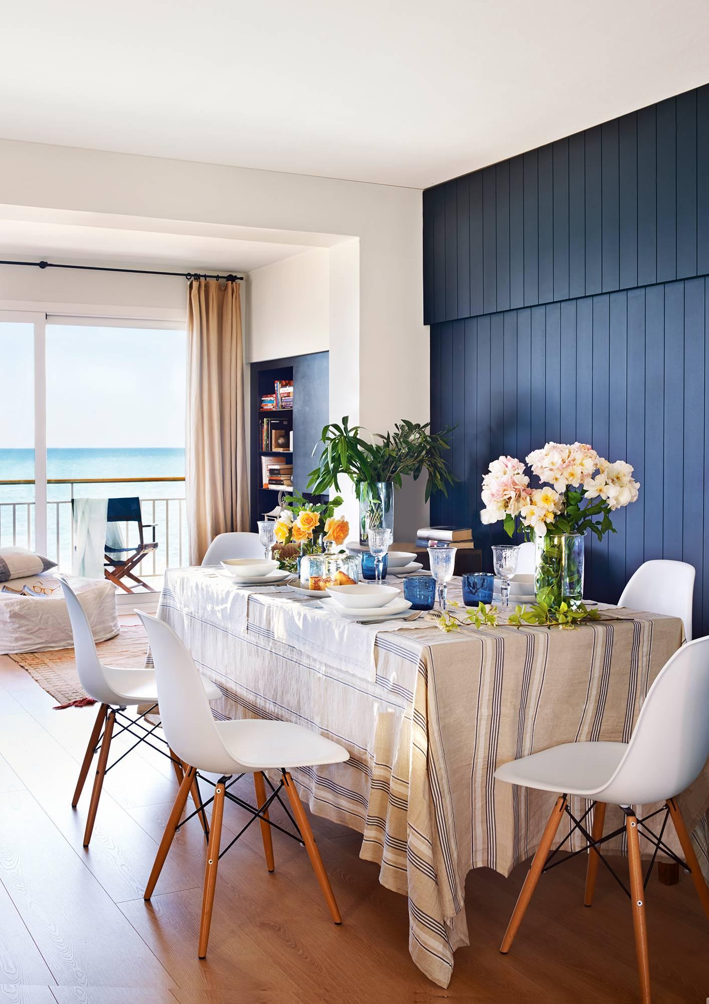 Comedor abierto al salón con pared revestida de lamas de madera en azul intenso_ 00407821. Tanto en azul intenso